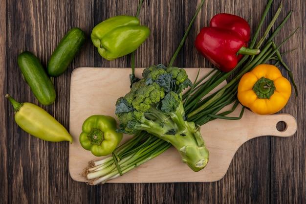 Vista dall'alto cetrioli con peperoni verdi broccoli e cipolle verdi su un tagliere su un fondo di legno