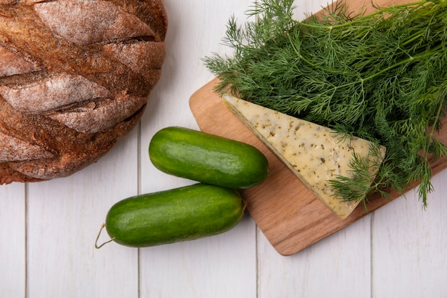Top view cucumbers with a loaf of black bread with cheese and dill  on a white background