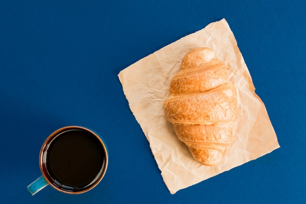 Top view of cup of black coffee and croissant on craft paper  with copy space. morning breakfast in french style.