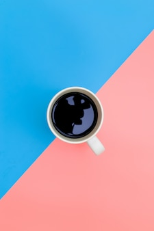 Top view of cup of black coffee on pink and blue background