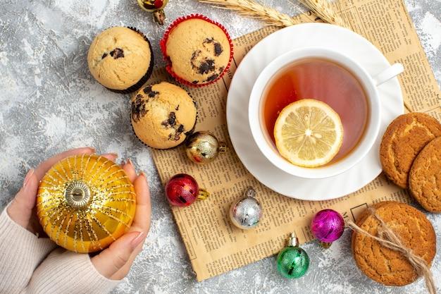 Vista dall'alto di una tazza di tè nero e accessori decorativi su un vecchio biscotto di giornale e piccoli cupcakes sulla superficie del ghiaccio