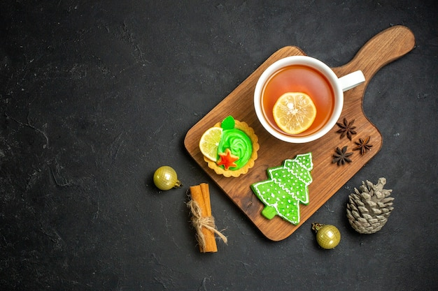 Vista dall'alto di una tazza di tè nero accessori capodanno cono di conifere e lime alla cannella su sfondo nero