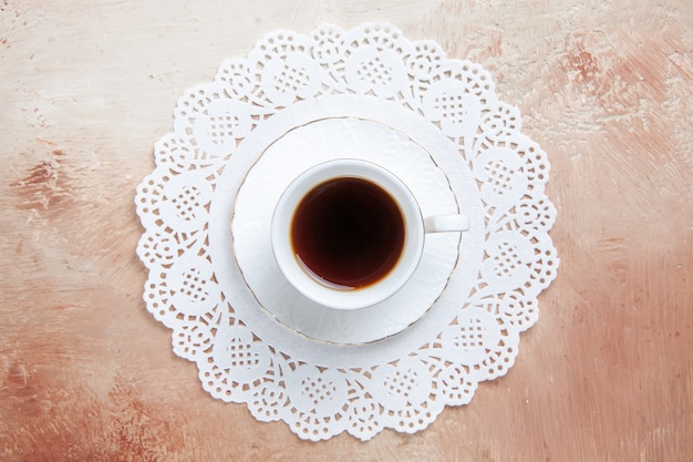 Top view of a cup of black tea on a white decorated napkin