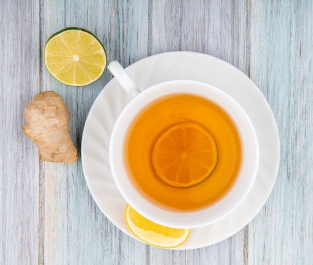 Top view of a cup of black tea with lemon slices with ginger on grey wood