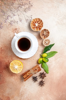 Top view of a cup of black tea with lemons and cinnamon sticks