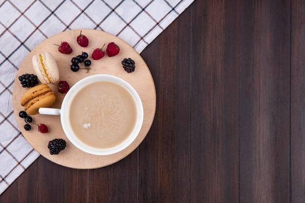 Vista dall'alto di una tazza di cappuccino con lamponi more ribes nero e macarons su un supporto su una superficie di legno