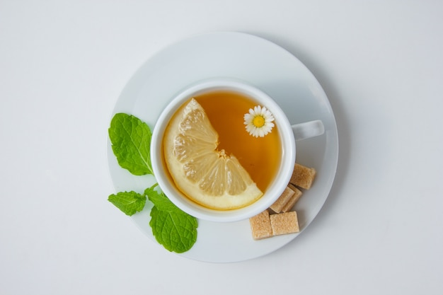 Top view a cup of chamomile tea with lemon, mint leaves, sugar on white surface. horizontal