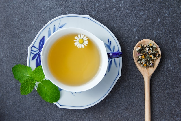Top view a cup of chamomile tea with mint leaves and chamomile herbs in spoon.