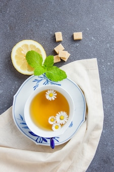 Top view a cup of chamomile tea with sugar, leaves, lemon on cloth