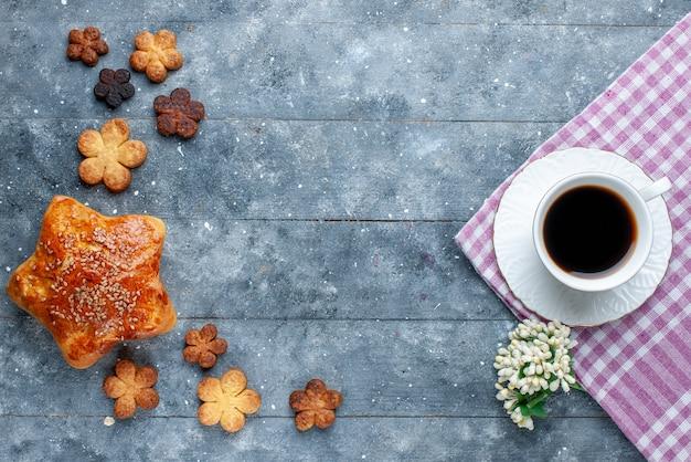 Vista dall'alto della tazza di caffè insieme a pasticceria e deliziosi biscotti sulla scrivania grigia, torta di zucchero da forno dolce