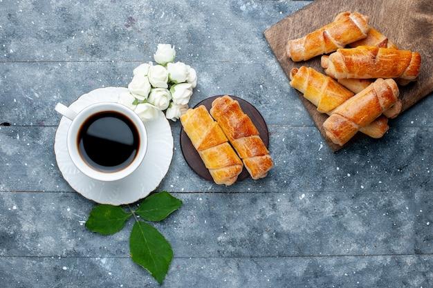 Vista dall'alto della tazza di caffè insieme a braccialetti deliziosi dolci su torta di pasticceria grigia e dolce
