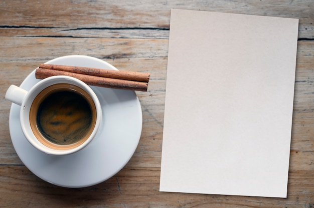 Top view cup of coffee and blank paper note on wooden table