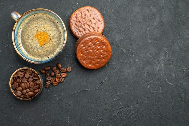 Top view a cup of coffee bowl with coffee seeds biscuits on dark isolated background