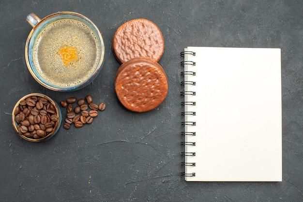 Vista dall'alto una tazza di caffè con biscotti di semi di caffè un blocco note su sfondo scuro isolato