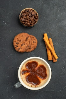 Top view a cup of coffee bowl with coffee seeds cinnamon sticks biscuits on dark isolated background