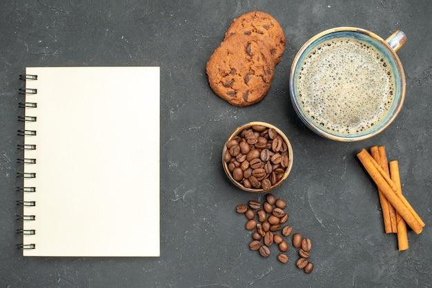 Vista dall'alto una tazza di caffè ciotola con semi di caffè bastoncini di cannella biscotti un taccuino su sfondo scuro isolato