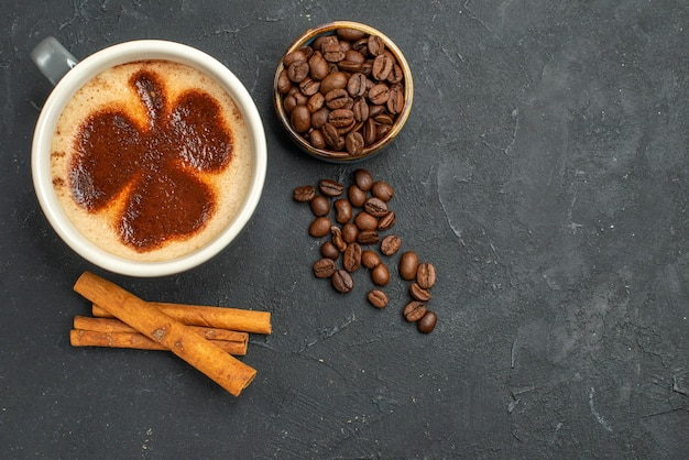 Top view a cup of coffee bowl with coffee seeds cinnamon sticks on dark isolated background