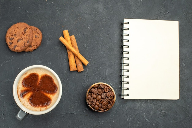 Top view a cup of coffee bowl with coffee seeds cinnamon sticks a notebook on dark isolated background