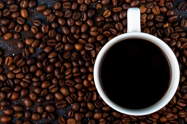 Top view of a cup of coffee on brown roasted coffee beans background