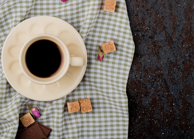 Top view of a cup of coffee and brown sugar cubes scattered on plaid tablecloth with copy space