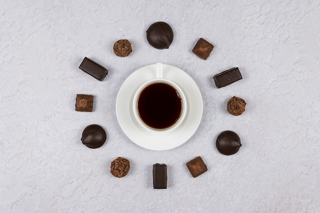 Top view of a cup of coffee and chocolate sweets on grey background. flat lay. concepts of morning time and alarm clock