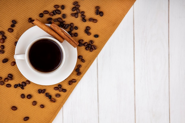 Top view of a cup of coffee on a cloth with cinnamon sticks with coffee beans on a white wooden background with copy space