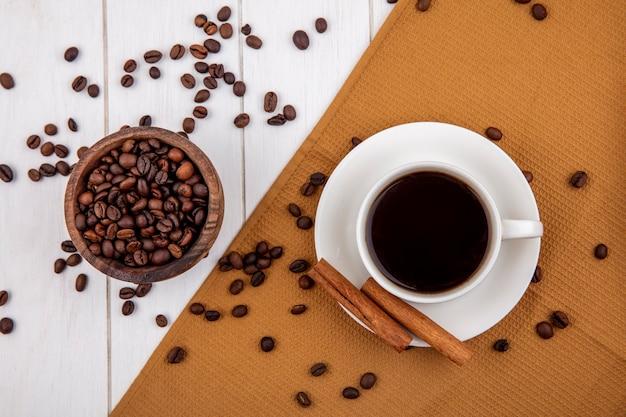 Vista dall'alto di una tazza di caffè su un panno con bastoncini di cannella con chicchi di caffè su una ciotola di legno su uno sfondo bianco