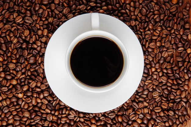Top view of a cup of coffee on coffee beans background