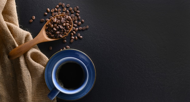 Top view of a cup of coffee and coffee beans on black background