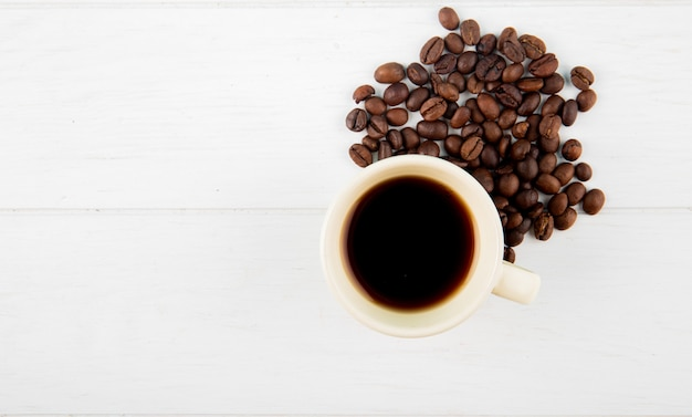 Top view of a cup of coffee and coffee beans scattered on white background with copy space