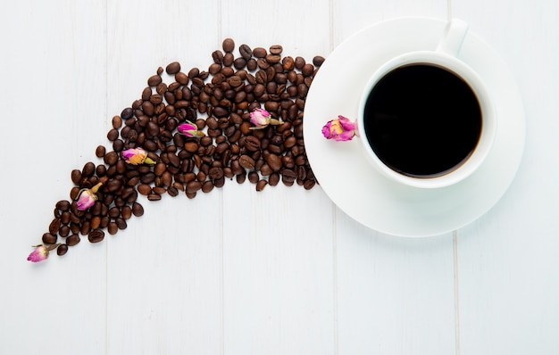 Top view of a cup of coffee and coffee beans scattered on white background