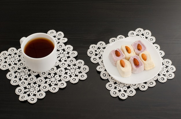 Top view of a cup of coffee and colorful turkish delight with almonds on the lace napkins black table