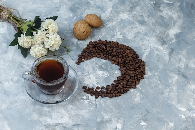 Top view cup of coffee, cookies with coffee beans, flowers on light blue marble background. horizontal