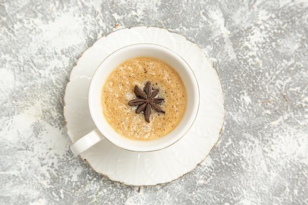Vista dall'alto tazza di caffè delizioso cappuccino all'interno della tazza sulla superficie bianca