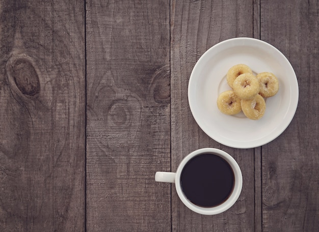 Top view, cup of coffee and donuts on wooden background.