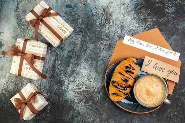 Vista dall'alto di una tazza di caffè e di un delizioso croissant fresco e belle scatole regalo per l'amato su una superficie scura