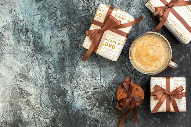 Top view of a cup of coffee and fresh stacked cookies beautiful gift boxes on dark surface