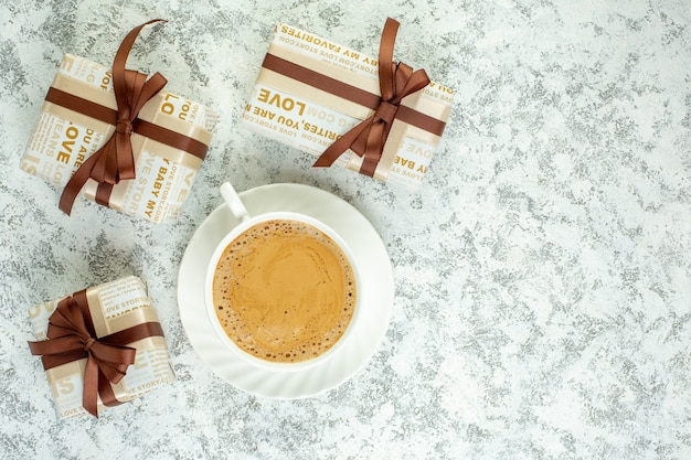 Top view cup of coffee gifts on grey table free space
