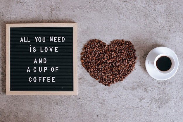 Top view of a cup of coffee and heart shape from coffee beans with quote on letter board, all you need is love and a cup of coffee