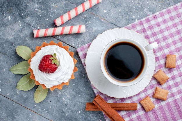 Vista dall'alto della tazza di caffè caldo e forte insieme a torta e cannella su grigio, biscotto al cacao bevanda dolce caramelle caffè
