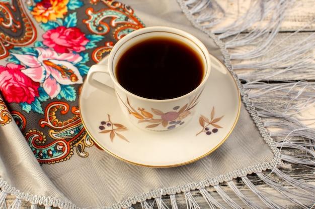 Vista superiore della tazza di caffè calda e forte sulla scrivania in legno grigio