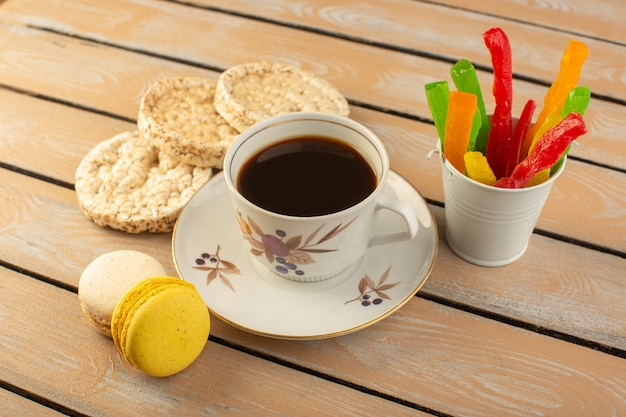 A top view cup of coffee hot and strong with french macarons and marmalade on the cream colored rustic table drink coffee photo biscuit