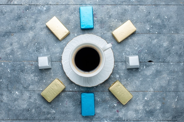 Top view of cup of coffee hot and strong with lined gold formed chocolate on blue, coffee cocoa drink hot
