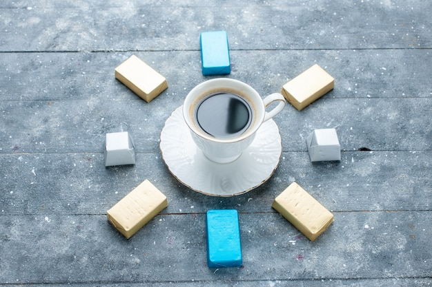 Top view of cup of coffee hot and strong with lined gold formed chocolate on light-blue desk, coffee cocoa drink hot