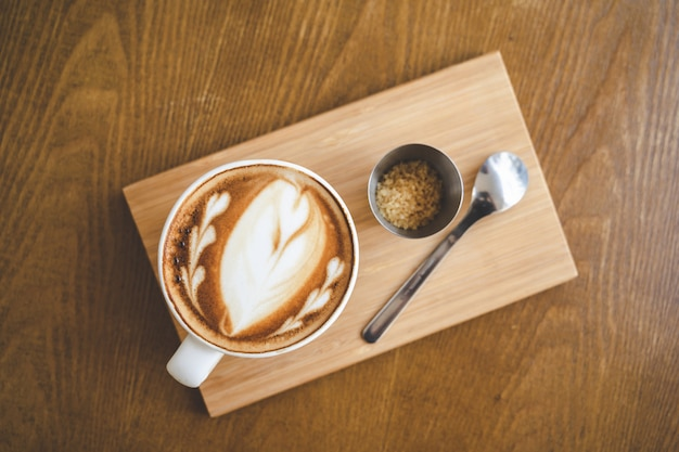 Top view a cup of coffee latte art in coffee shop cafe on wood board