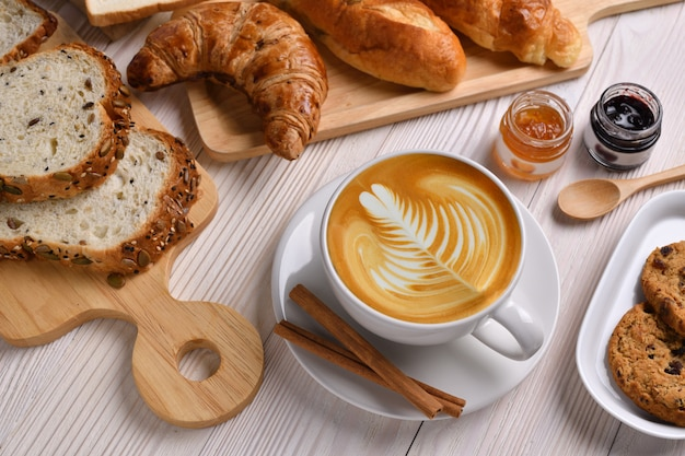 Top view of cup of coffee latte with breads or bun, croissant and bakery on white wooden table