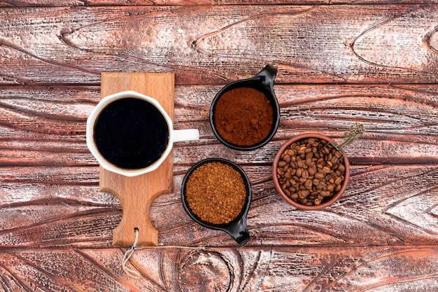 Top view cup of coffee on little wooden board coffee beans on  wooden surface