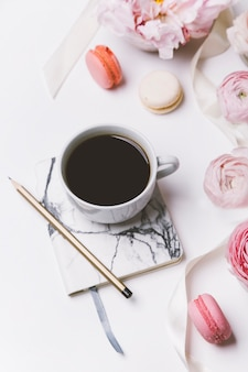 Top view of cup of coffee and peony flowers on white background