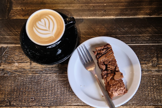 Top view of a cup of coffee and plate of chocolate cake on a wooden table