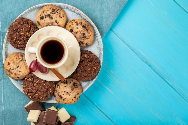 Top view of a cup of coffee served with oatmeal cookies and chocolate on blue background with copy space